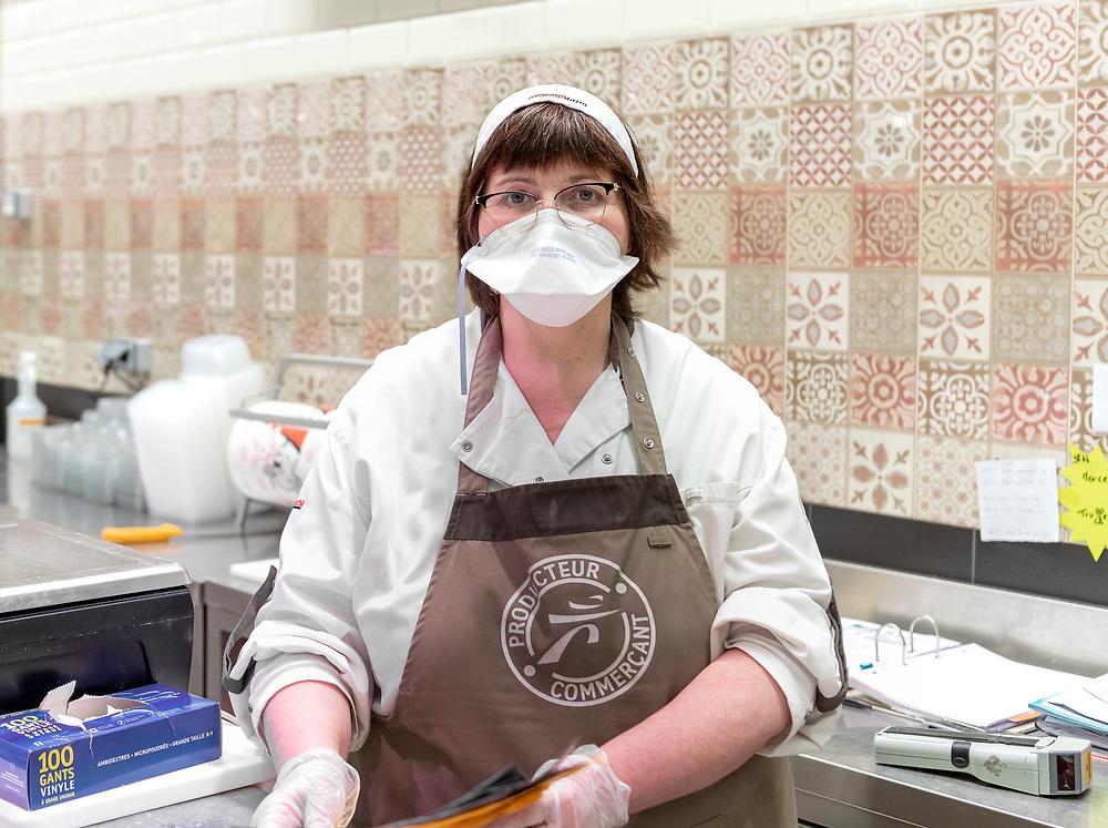 """Portrait de la charcutière avant l'ouverture du supermarché """"INTERMARCHÉ"""", La Loupe, région Centre, France, le 19 mars 2020.<br /> Portrait of the butcher before the supermarket opens."""