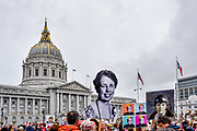 The crowd of marchers gather at Civic Center Plaza in front of San Francisco City Hall with signs of famous change-making women held in the air beside the dome, including Eleanor Roosevelt, Ruth Bader Ginsburg and Amelia Earhart.
