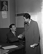 """05/01/1953<br /> 01/05/1953<br /> 05 January 1953<br /> Garda Dick Farrelly, song writer at College Street Garda Station, Dublin. On right is Paddy Kearney, Singer. Garda Farrelly is being congratulated that his piece """"The Isle of Innisfree"""" had been used in the film """"The Quiet Man""""."""