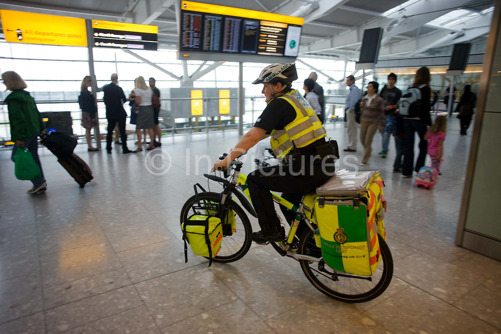 """NHS Paramedic Janet Greenhead cycles through the departures concourse on her Specialized Rockhopper mountain bike in Heathrow Airport's Terminal 5. Janet is a Responder with the cycle response unit (CRU), a part of the London Ambulance Service whose job it is to attend injuries within Heathrow's terminals. Pedalling the heavy bike laden with 55kg of medical emergency equipment she answers the calls from those with a cut finger, a baggage handler who's injured an arm, a child who's fallen over with cuts and bruises or a much more serious incident like a cardiac arrest which are common in an airport where passengers feel under stress or who forget to take their medicines while jet lagged. During a busy shift, she could end up cycling more than eight miles. From writer Alain de Botton's book project """"A Week at the Airport: A Heathrow Diary"""" (2009). ."""