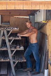 shirtless muscular man without a shirt in a garage