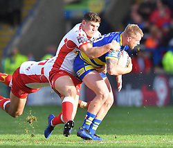 Warrington Wolves' Mike Cooper is tackled by Hull Kingston Rovers' Robbie Mulher and Mose Masoe during the Betfred Super League match at the Halliwell Jones Stadium, Warrington.