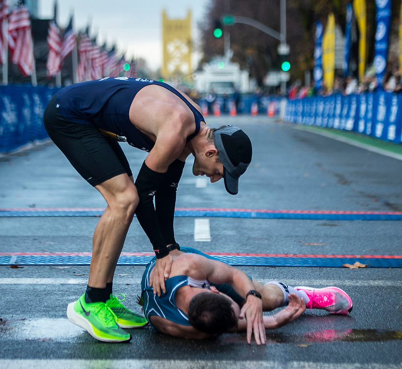 Dylan Marx checks on Zachary Nine after he collapses after crossing the finish line at the California International Marathon in downtown Sacramento, Sunday, Dec. 8, 2019.
