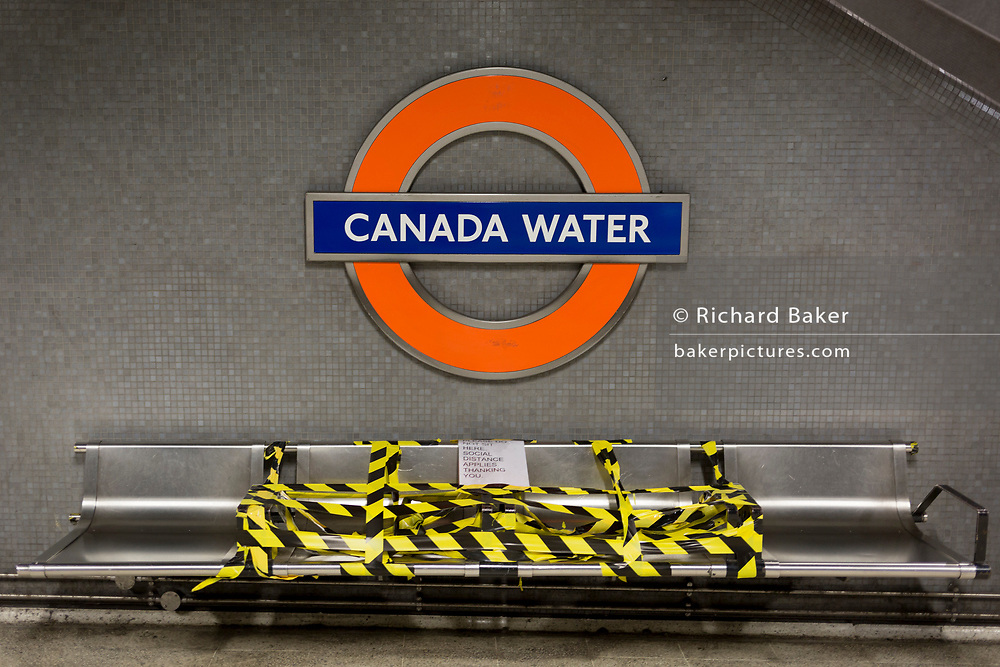As the UK's Conornavirus pandemic lockdown continues, but with travel restrictions and social distancing rules starting to ease after three months of closures and isolation, hazard tape blocks some seating beneath the station name, at London Underground's Canary Water station, on 9th June 2020, in London, England.