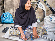 "08 AUGUST 2013 - BANGKOK, THAILAND:       A Muslim woman waits to receive alms from people going to Haroon Mosque in Bangkok for Eid al-Fitr services. Eid al-Fitr is the ""festival of breaking of the fast,"" it's also called the Lesser Eid. It's an important religious holiday celebrated by Muslims worldwide that marks the end of Ramadan, the Islamic holy month of fasting. The religious Eid is a single day and Muslims are not permitted to fast that day. The holiday celebrates the conclusion of the 29 or 30 days of dawn-to-sunset fasting during the entire month of Ramadan. This is a day when Muslims around the world show a common goal of unity. The date for the start of any lunar Hijri month varies based on the observation of new moon by local religious authorities, so the exact day of celebration varies by locality.  PHOTO BY JACK KURTZ"