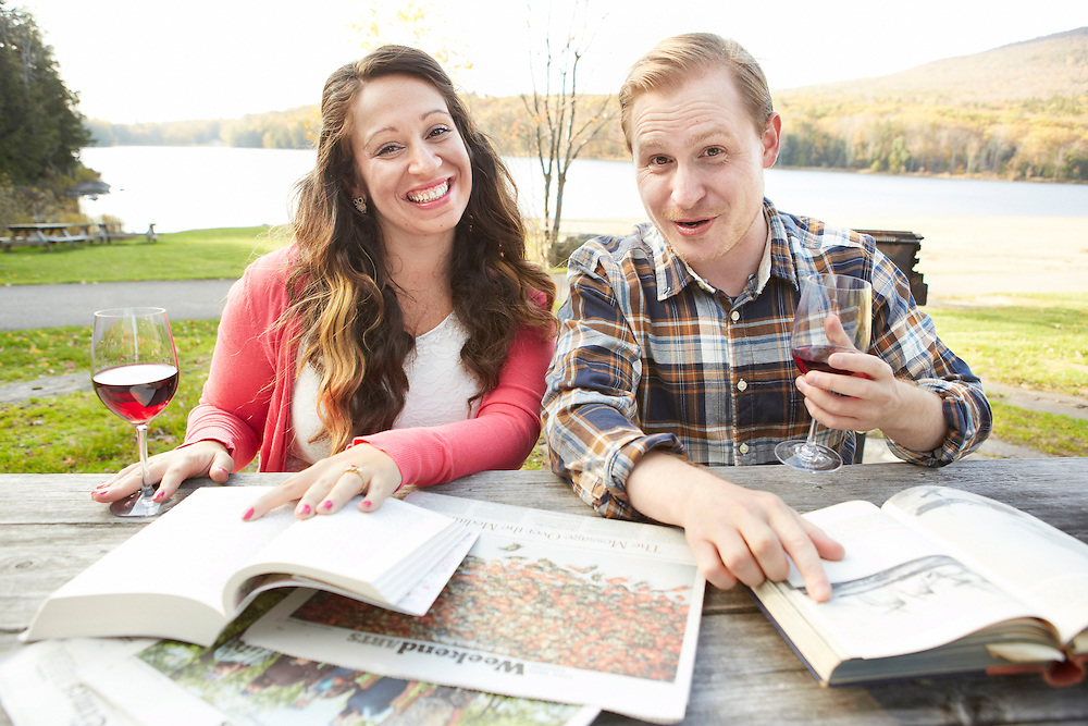 Lifestyle image of fun couple drinking red wine outside during autumn while reading books and newspapers