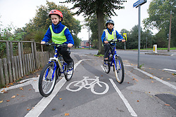 Two children cycling to school on a designated path,