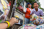 08 SEPTEMBER 2013 - BANGKOK, THAILAND: A boy in his school uniform laughs while he helps load donated food and supplies into a truck after a mass alms giving ceremony in Bangkok Sunday. Volunteering time to do good works is a form of merit making in Thai culture. 10,000 Buddhist monks participated in a mass alms giving ceremony on Rajadamri Road in front of Central World shopping mall in Bangkok. The alms giving was to benefit disaster victims in Thailand and assist Buddhist temples in the insurgency wracked southern provinces of Thailand.      PHOTO BY JACK KURTZ