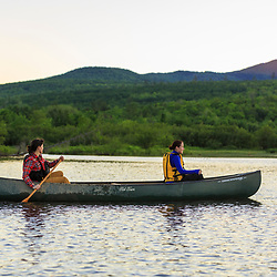 Two women paddle a canoe at dawn on Silver Lake in Piscataquis County, Maine. Near Greenville.