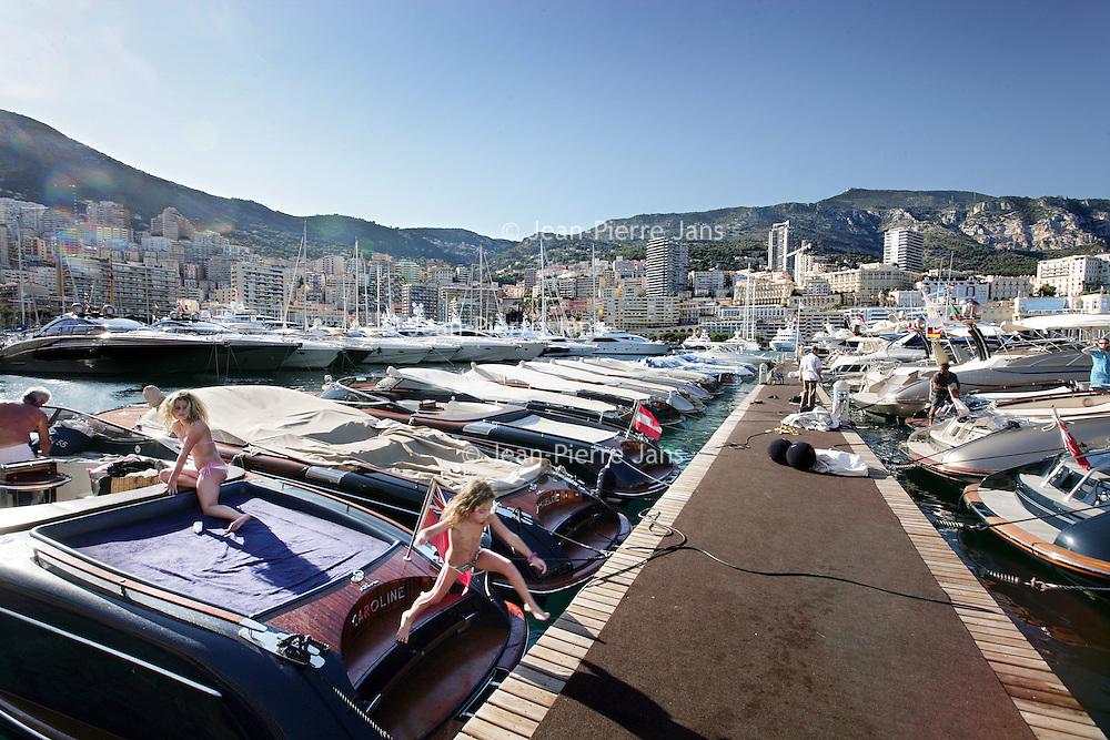 Monaco, 6 augustus 2009. .De haven van Monaco, gelegen in het stadsdeel Condamine, is gekend door de vele superjachten en cruiseschepen die er aangemeerd liggen, het een al luxueuzer dan het andere. De Grand Prix van Monaco begint en eindigt hier ieder jaar..Het staatje Monaco grenst aan Frankrijk en de Middellandse Zee. Monaco heeft een oppervlakte van nog geen 2 km en heeft ongeveer 32. 000 inwoners. Daarmee is Monaco het dichtstbevolkte land ter wereld. Monaco telt twee steden: Monte-Carlo en Monaco-ville, de oude stad..Foto:Jean-Pierre Jans..Monaco, 6th august 2009. The Port of Monaco in the Condamine District, with many very luxurious super yachts  and cars. A girl in company with her parents jumps from their yacht.
