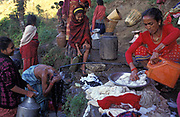 Local women fill water bottles and wash family clothing and their hair in cold Himalayan mountain waters during their morning ritual in Gorkha which lent its name to the Gurkha soldier, and from where young teenage boys are typically recruited for service into the British army, a tradition that goes back to the Indian Mutiny of 1857, on 12th December 1997, in Gorkha, Nepal.