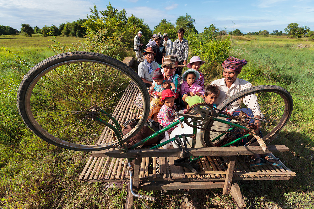 """A family travel on the """"Bamboo Train' in Battambang, Cambodia. The railway is no longer used by passenger trains but local people have built bamboo platforms which rest upon old train wheels, allowing them to still travel on the rails."""