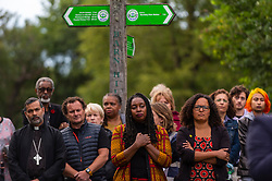 © Licensed to London News Pictures. 03/08/2021. LONDON, UK. Dawn Butler MP for Brent Central, (C), at a vigil at Barn Hill Pond, Fryent Country Park near Wembley to remember the lives of sisters Bibaa Henry and Nicole Smallman, on what would have been Nicole's 29th birthday.  The sisters were murdered in the park in June 2020 whilst celebrating Bibbaa's birthday.  Reclaim These Streets have worked with former Archdeacon of Southend, the Ven. Wilhelmina (Mina) Smallman, the late sisters' mother, to organise the vigil and attendees were encouraged to wear green and purple, the sisters' favourite colours, or light a candle.  Photo credit: Stephen Chung/LNP
