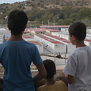 Three refugee children, Youssef, 14, Rebas, 9, and Diar, 13, looking over the Leros 'Hotspot', an EU-run migrant's reception centre opened in the grounds of the former Lepida psychiatric hospital. <br /> <br /> The Hot Spot in Lepida opened on the 26th of February 2016 in the grounds of the former Lepida psychiatric hospital.  At the beginning it served as a registration camp for refugees and migrants who were travelling to Europe through Greece but since the closure of the borders in March 2016 it serves as a permanent camp. People are allowed to go out, they have three meals a day, the prefabricated huts have a bathroom and are air-conditioned and compering to other refugee camps in Greece the conditions are bearable.