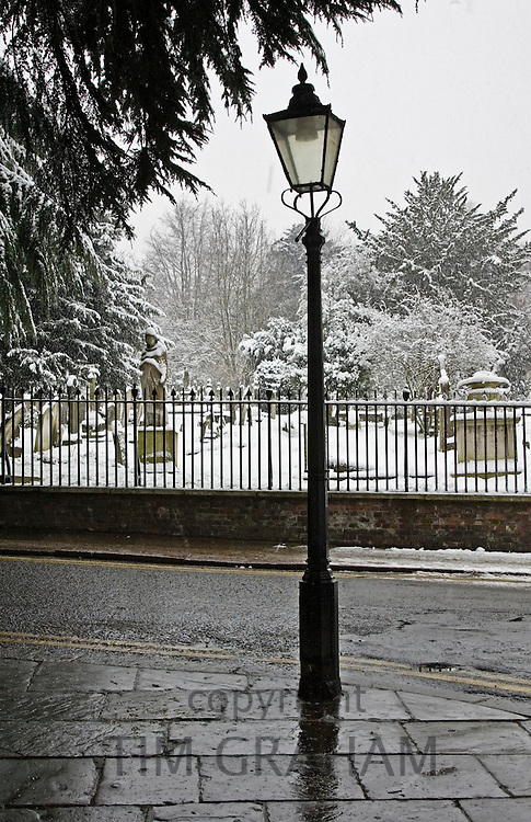 Street lamp besides snow covered graveyard, North London, United Kingdom