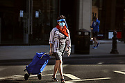 Masked woman crossing Knightsbridge, deserted during the Coronavirus pandemic on 23th April 2020 in London, United Kingdom. The government clampdown includes the closure of most shops, bars and theatres throughout the country.