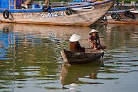 Two women in a boat rowing across the Thu Bon river in Hoi An, Vietnam.