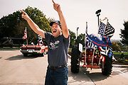 26 SEPTEMBER 2020 - DES MOINES, IOWA: GARY LEFFLER, an organizer of the motorcade supporting the reelection of Donald J. Trump, waves to people in the motorcade as it passes the Iowa State Capitol. More than 1,500 people in 500 vehicles participated in motorcade through Des Moines Saturday. They started in the suburbs south of downtown, drove through downtown, and ended at the State Capitol.        PHOTO BY JACK KURTZ