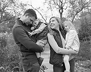 Black and white family portrait at Acton Arboretum. Family interacting with each other while mom and dad hold each child and the dog between them.