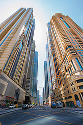 Street lined with new skyscrapers in Dubai United Arab Emirates