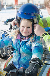 Portrait of girl helped by man in wearing helmet