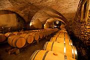 Barrels of wine aging in the cellars of Château La Nerthe Vineyard, France