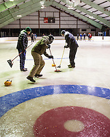 "Jim McShane looks on as ""sweepers"" Mike Dowe and Herb Greene try to get their teams yellow stone into the circle during the weekly curling tournament at Gilford Ice Rink with Gilford Parks and Rec on Thursday evenings.  (Karen Bobotas/for the Laconia Daily Sun)"