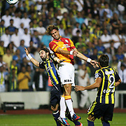 Galatasaray's player Johan Elmander (C) during the head stroke to the ball between the Fenerbahce's players on their Turkish Super Cup 2012 soccer derby match Galatasaray between Fenerbahce at the Kazim Karabekir stadium in Erzurum Turkey on Sunday, 12 August 2012. Photo by TURKPIX