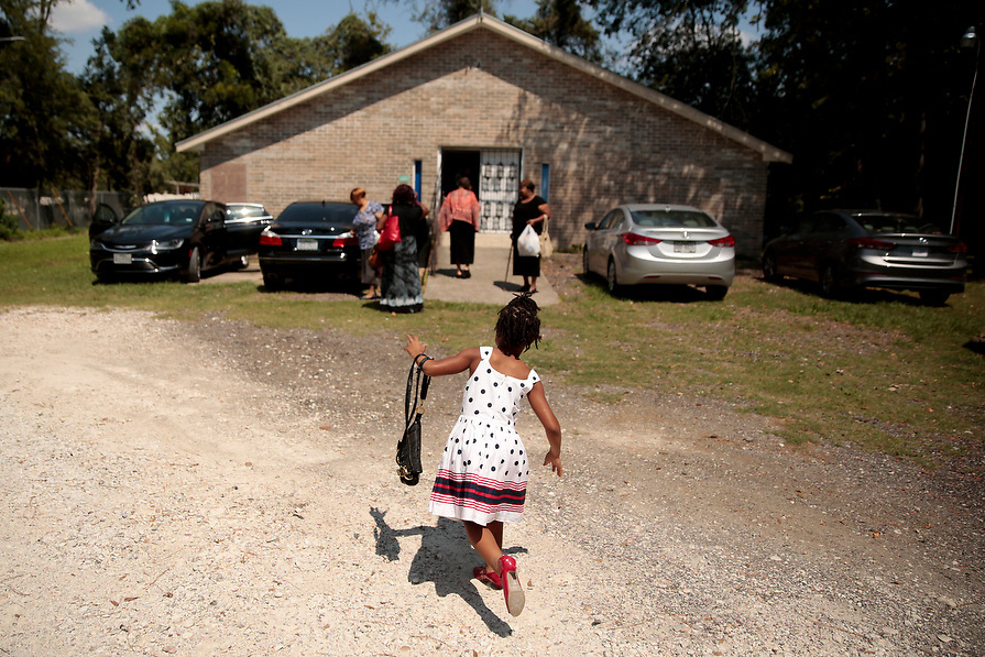 """Melanie Thomas, 7, wears a donated dress and shoes at the Sunday service at True Vine Missionary Baptist Church in the aftermath of tropical storm Harvey in Houston, Texas, U.S. September 10, 2017. Her family lost all of their belongings in the flood and are living at a hotel with the assistance of FEMA. """"Momma I'm happy as long as we're together,"""" said Thomas."""