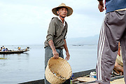 Intha fisherman selling fish from his boat on Inle Lake on 22nd January 2016, Shan State, Myanmar.  Most Intha people get around on the lake using traditional flat-bottomed skiffs propelled by a single wooden paddle. The Intha technique of leg rowing - where one leg is wrapped around the paddle to drive the blade through the water is unique