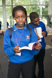 Secondary School girl selecting book from the library at lunch break,