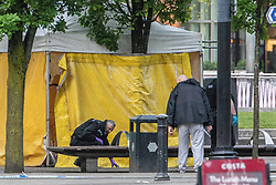 © Licensed to London News Pictures . 03/05/2019. Manchester, UK. Police search the scene . Police have cordoned off several square blocks around Piccadilly Gardens in Manchester City Centre following concern that a device . A tent has been erected and a man has been arrested in connection with the incident . Oldham Library has also been evacuated on what is believed to be a connected incident . Photo credit: Joel Goodman/LNP