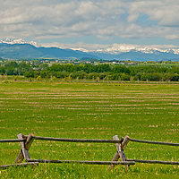 Fair weather cumulus clouds drift over pastures in Montana's Gallatin Valley, near Bozeman.  The Spanish Peaks (L) and Tobacco Root Mountains (R) rise in the background.