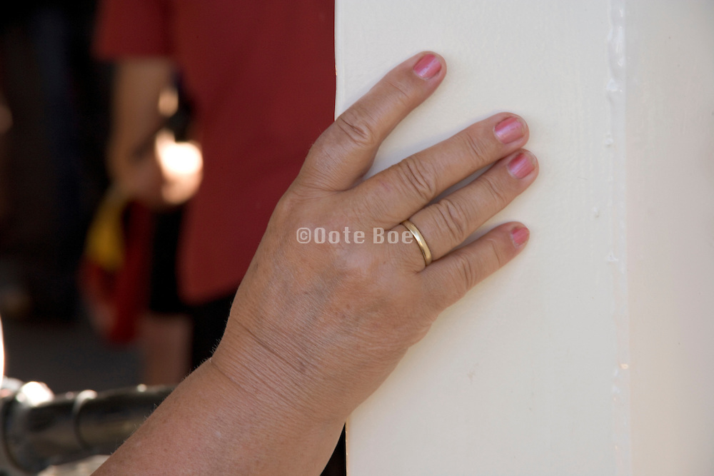 chubby hand of a middle aged woman holding on to the door post