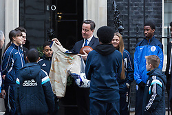 © Licensed to London News Pictures. 11/12/2014. London, UK. British Prime Minister, David Cameron and Culture secretary, Sajid Javid, meet a group of young footballers outside 10 Downing Street in London on 11th December 2014. The players and Premier League representatives will be taking part in the 100th anniversary of the First World War Truce match in Ypres. Photo credit : Vickie Flores/LNP