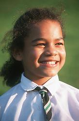 Portrait of young girl wearing school uniform smiling,