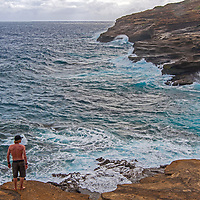 A visitor watches Pacific Ocean waves rolling into the southeast coast of Oahu, Hawaii.