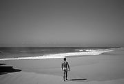 muscular naked man walking towards the Pacific Ocean on a deserted beach