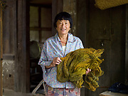 Namgay Pedon holding naturally dyed wild silk to be woven into a kira the Bhutanese women's traditional floor length dress, Rangjung village, Eastern Bhutan.