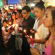 People are seen as they hold candles during a vigil at the Dr. Phillips Center for the Performing Arts for the victims of a mass shooting at the Pulse nightclub Monday, June 13, 2016, in Orlando, Florida.  A gunman killed dozens of people in a massacre at the crowded gay nightclub in Orlando on Sunday, making it the deadliest mass shooting in modern U.S. history. (Alex Menendez via AP)