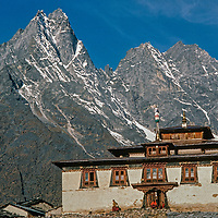 Sacred Mount Khumbila rises behind monks at Tengboche Monastery, a spiritual center for the Sherpas of Nepal. This picture was shot in 1986 before the monastery was destroyed in an 1989 electrical fire and subsequently rebuilt in a more modern form.