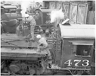 """Shop crew repairing steam dome valve on #473 outside Durango roundhouse.  #497 is in the background.  <br /> D&RGW  Durango, CO  Taken by Payne, Andy M. - 4/16/1971<br /> In book """"Durango: Always a Railroad Town (1st ed.)"""" page 38<br /> Also in """"Grande Gold"""", p. 31."""