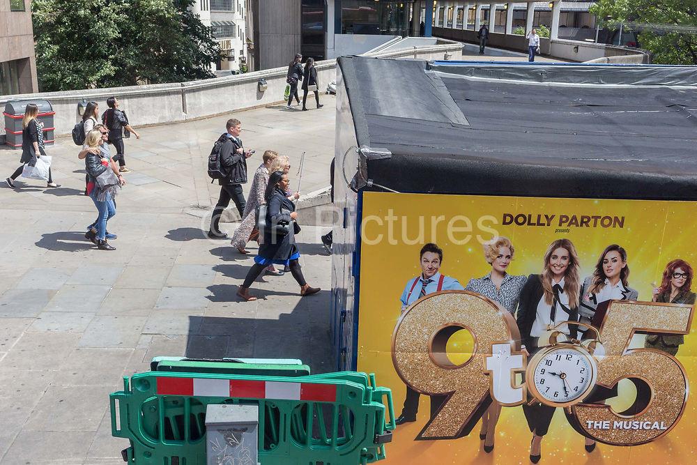Commuters walk over London Bridge passing a billboard for the musical Nine to Five presented by its original star Dolly Parton, on 17th June 2019, in London, England.