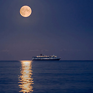 The Harvest Moon rises above Cunard's Queen Victoria as she sits at anchor in Weymouth Bay. The cruise industry has suffered a complete shutdown during the covid-19 pandemic and many vessels are currently waiting at various anchorages around the coast of Great Britain and the world.<br /> Picture date Tuesday 1st September, 2020.<br /> Picture by Christopher Ison. Contact +447544 044177 chris@christopherison.com