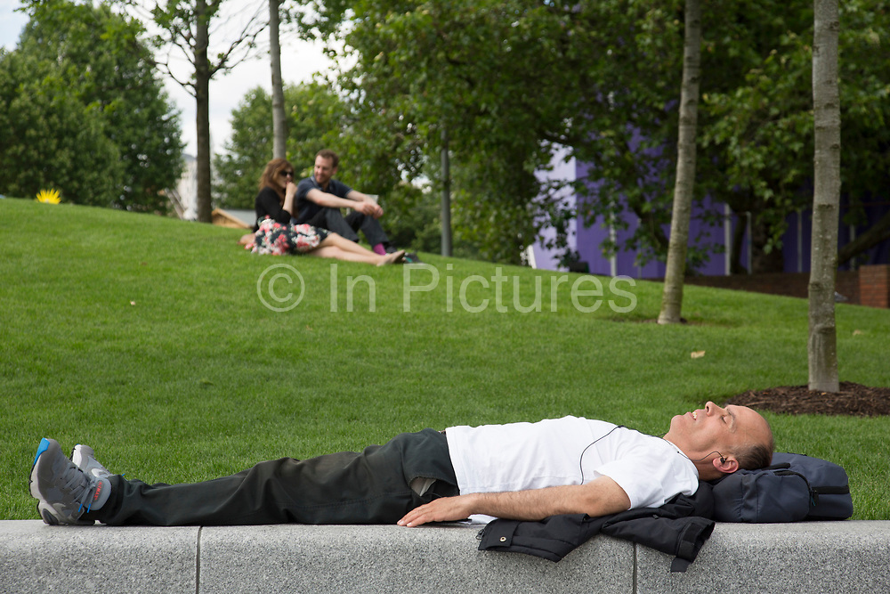 Man sleeping in the summer sunshine at Jubillee Gardens on the South Bank in London, UK. The South Bank is a significant arts and entertainment district, and home to an endless list of activities for Londoners, visitors and tourists alike.