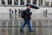 Photographer Nils Jorgensen walks beneath the columned architecture of the National Gallery in Trafalgar Square, Westminster, on 9th April 2019, in London, England.