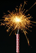 Burning firecracker fuse with sparks flying against a black background