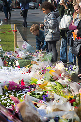 Parliament Square, Westminster, London, June 17th 2016. Following the murder of Jo Cox MP friends and members of the public lay flowers, light candles and leave notes of condolence and love in Parliament Square, opposite the House of Commons. PICTURED: A boy lays a floral tribute among scores of others.