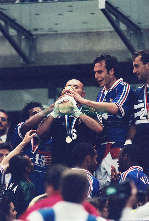 France's goalkeeper Fabien Barthez, flanked by Alain Boghossian and Christian Karembeu, kisses the trophy after the FIFA football world cup France v Brazil final match at the Stade de France stadium in Saint-Denis, near Paris, France, July 12, 1998. France won 3-0. Photo by Lionel Hahn/ABACAPRESS.COM