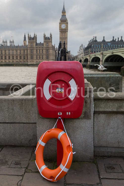 In the year that Britain will start the process of Brexit leaving the European Union, a lifebuoy lies dangling on the ground with the River Thames and the British Houses of Parliament in the background -  a scene of chaos, risk and jeopardy, on 2nd february 2017, in London, England.